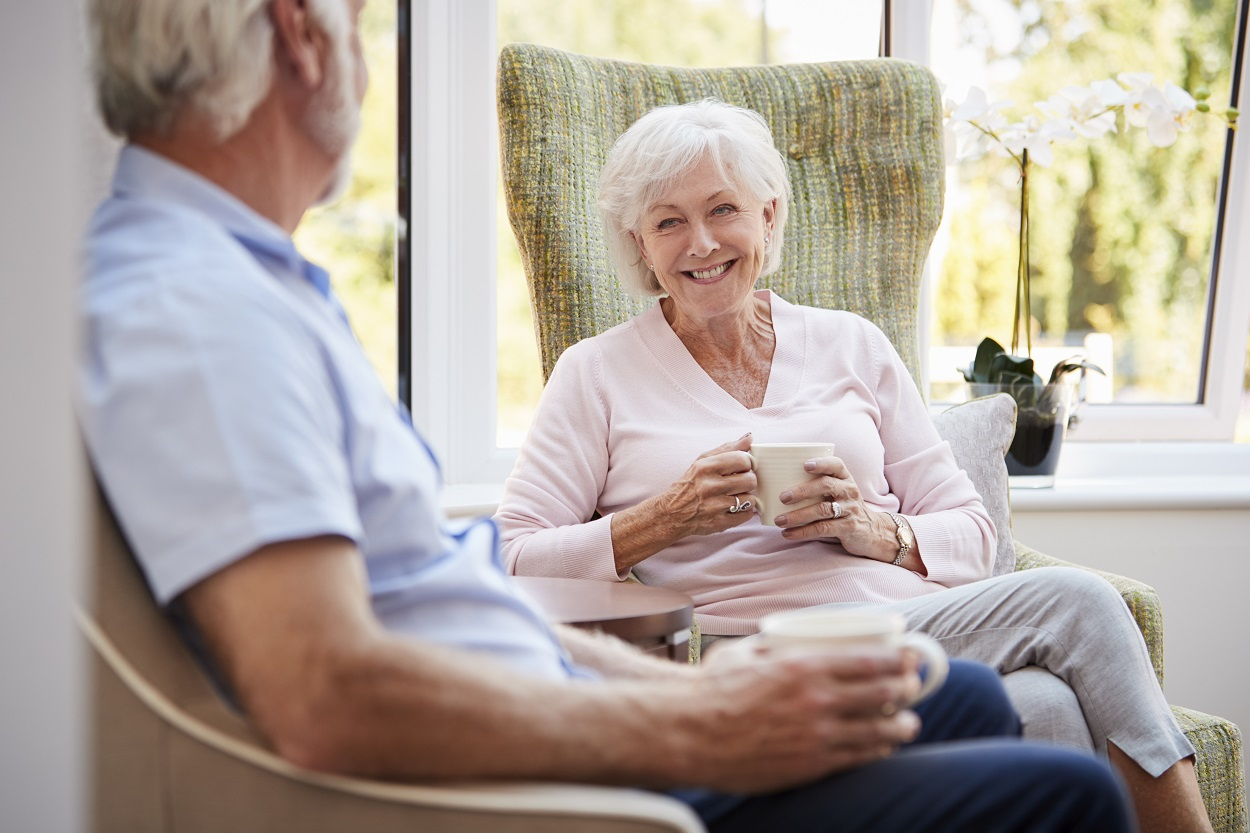 Senior couple sitting and chatting at retirement home